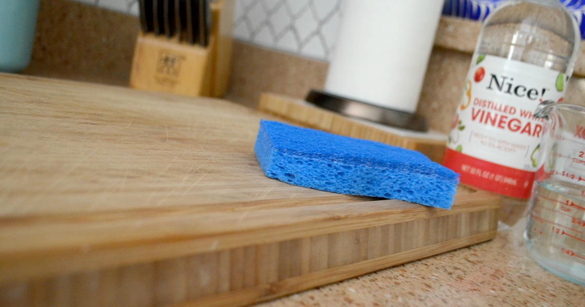 vinegar and a sponge on a wooden cutting board