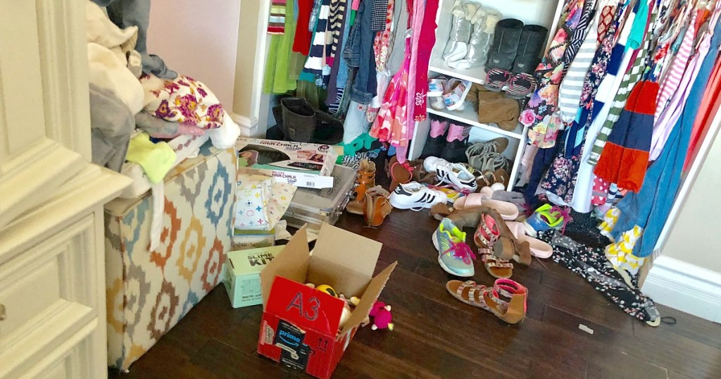 girls closet cluttered with boxes, shoes, clothes, etc.