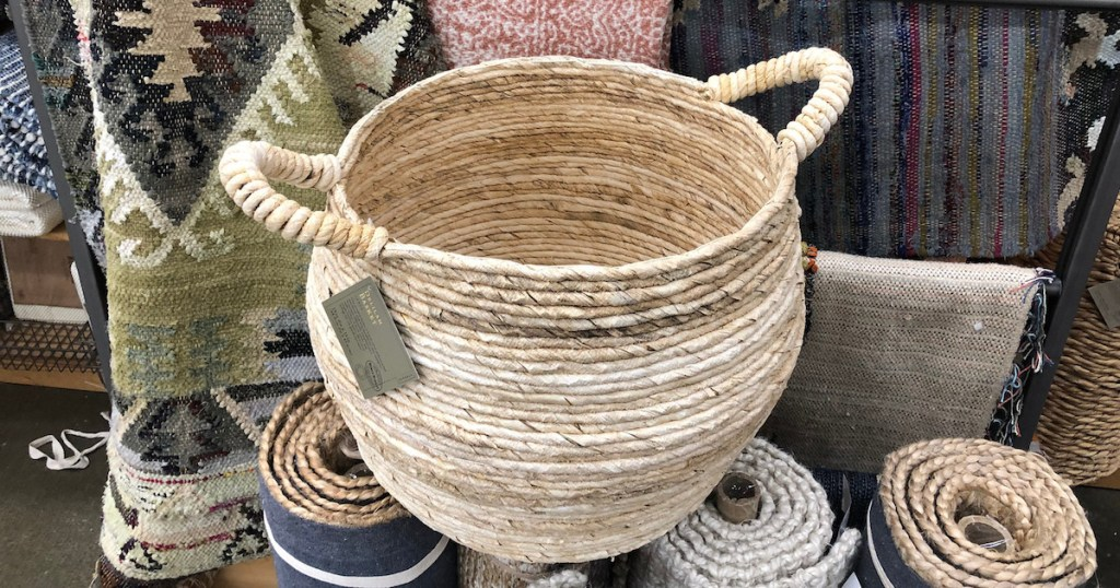 round woven basket with handles sitting on a pile of rugs