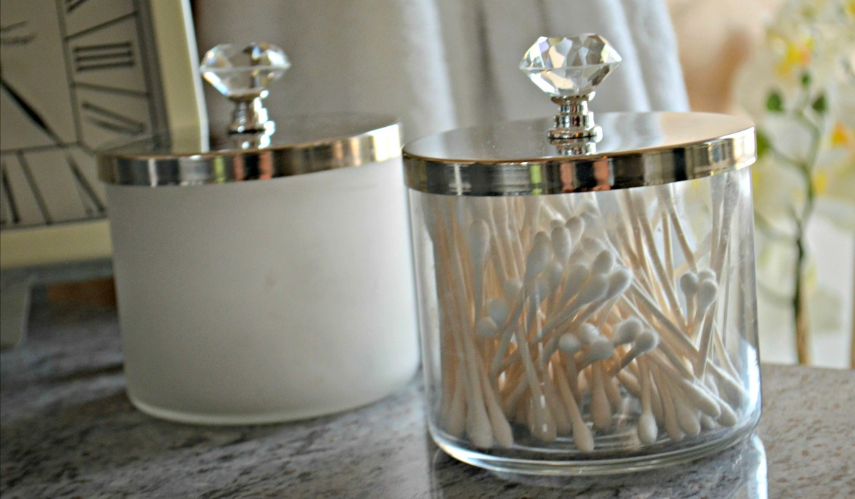 repurposed candle jars being used for bathroom vanity storage