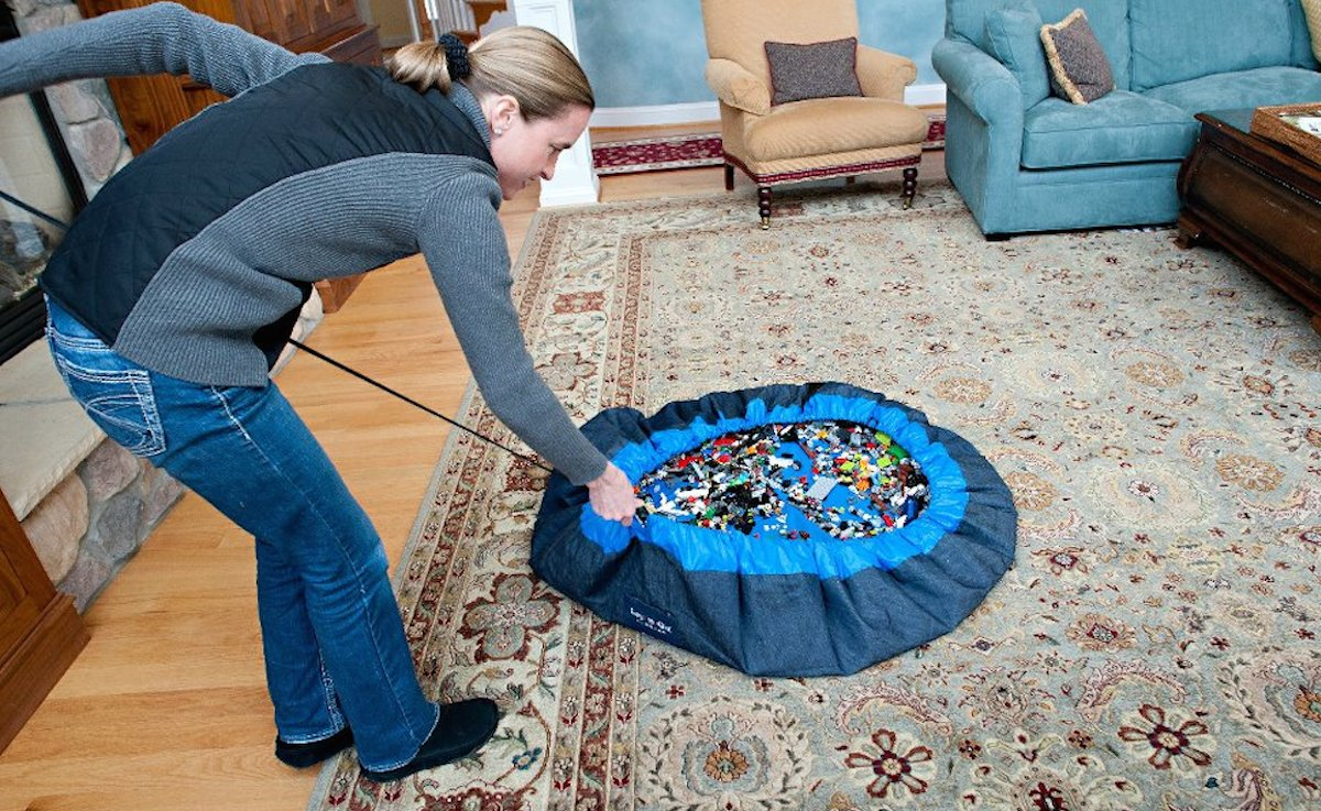 mom closing a blue drawstring bag with small legos inside of living family room