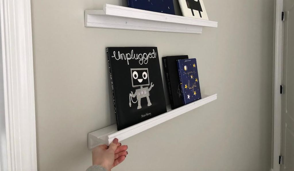 two white ikea floating shelves with books on them