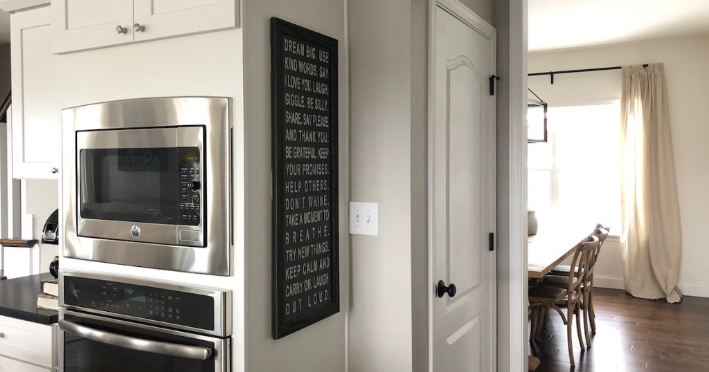 white kitchen cabinets with wall oven and hanging picture frame artwork on cabinets