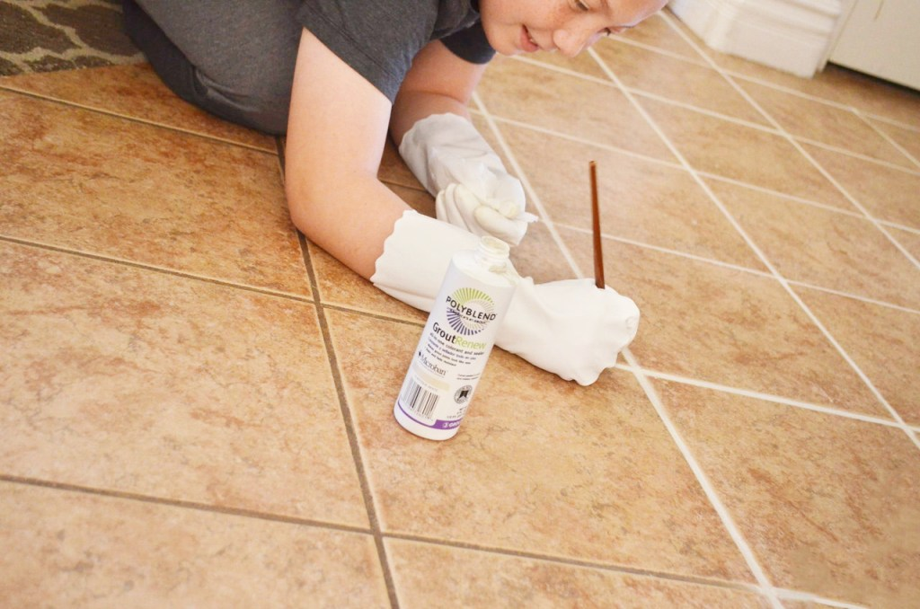 young boy holding paint brush kneeing on tile floor painting grout white