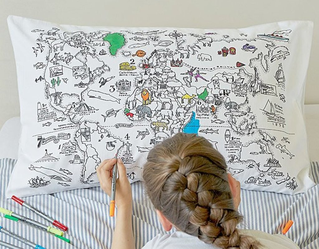 girl with braided hair coloring on map pillowcase