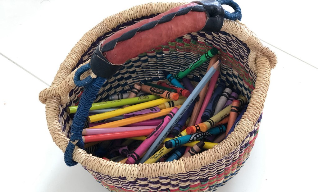 colorful market basket with leather handle on desk with colored pencils and crayons inside