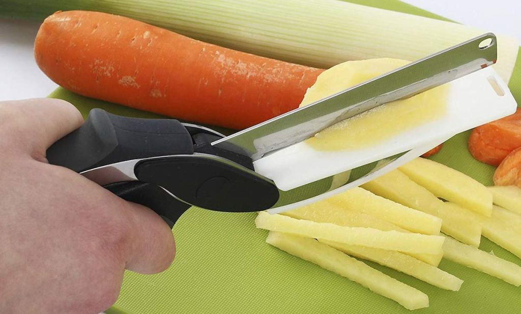 hand using scissors with cutting board to chop veggies