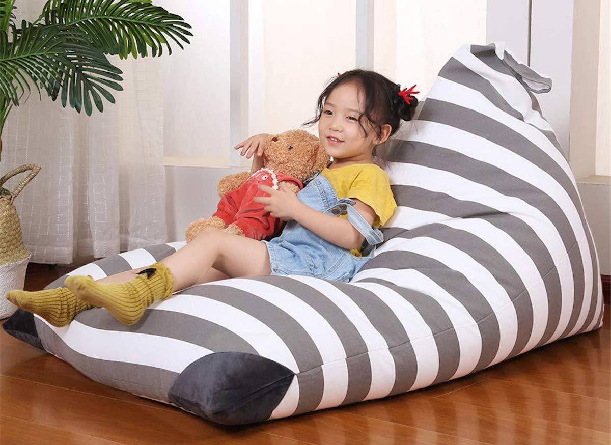 gray and white stripe bean bag chair with girl holding a stuffed bear