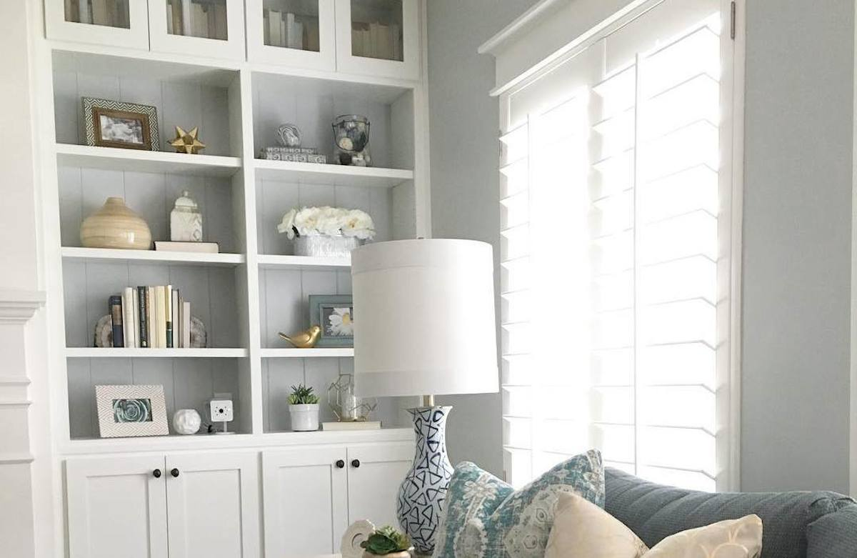 white bookshelves with decor and gray walls with a lamp and couch in front of window