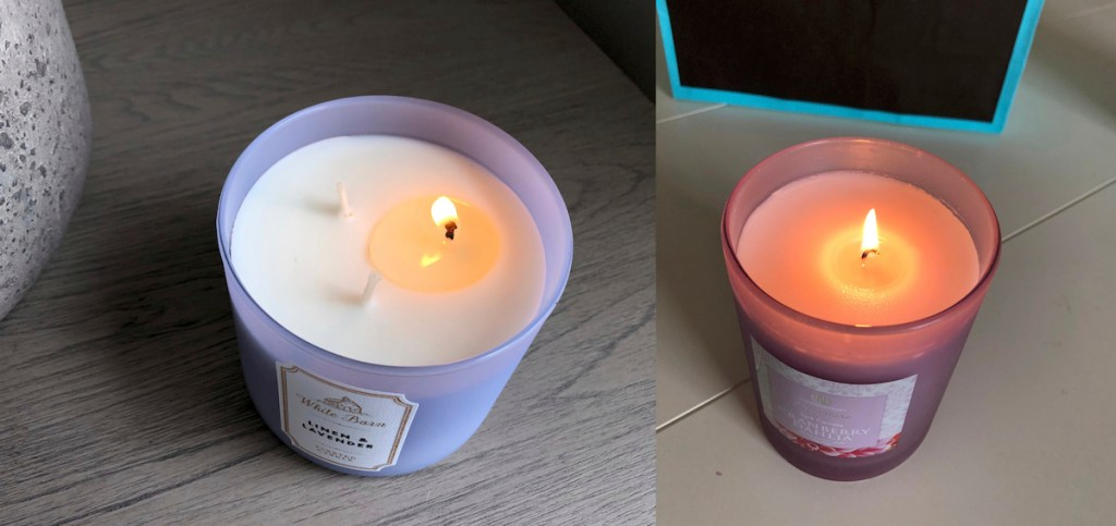 two purple candles with one wick on each burning