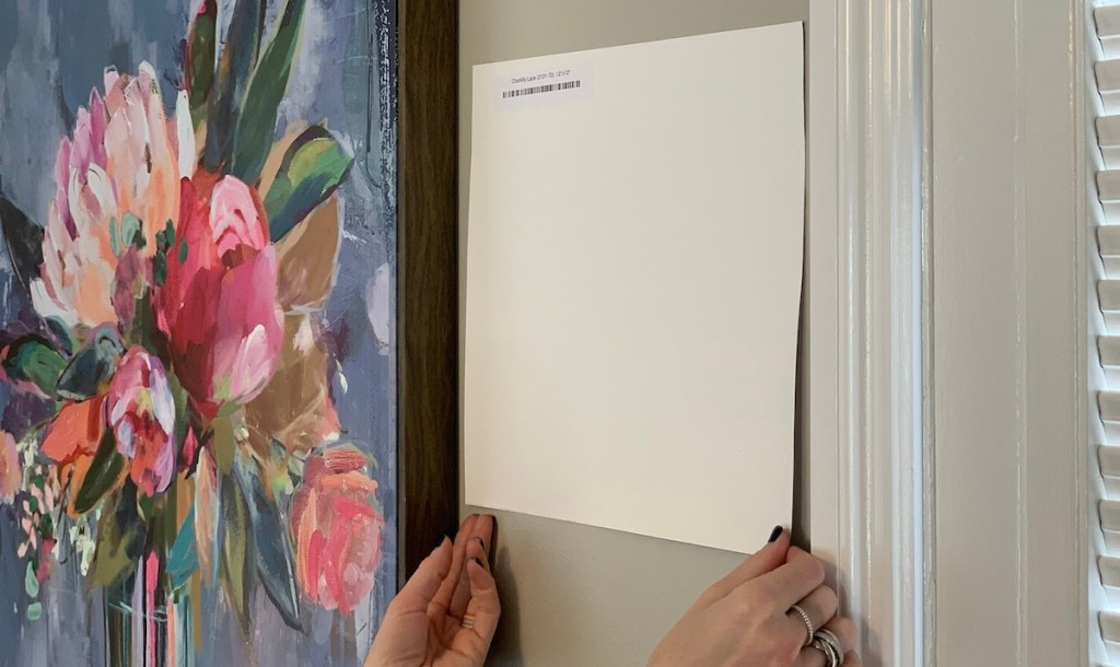 two hands holding corners of white square paint sample next to floral artwork