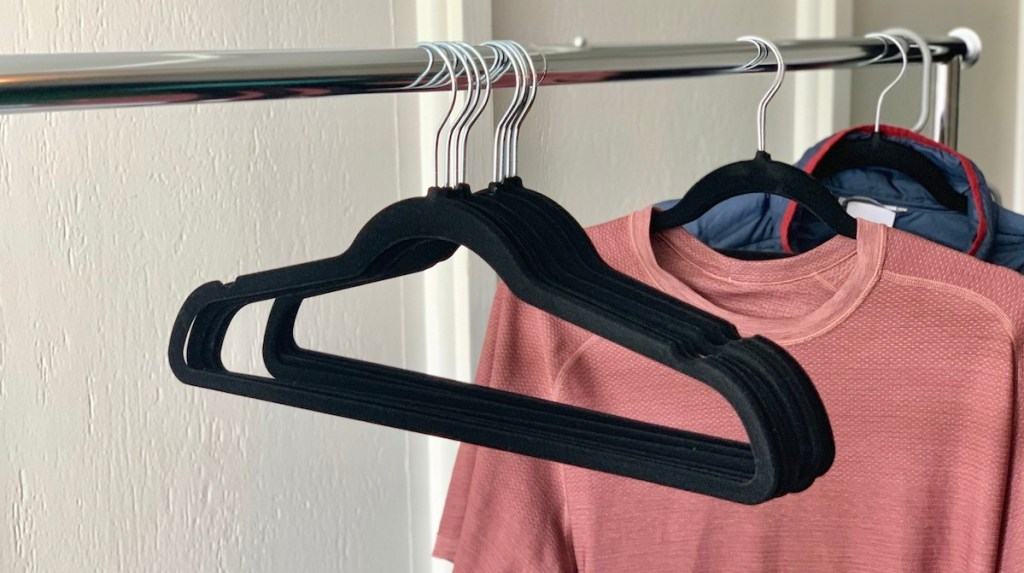 black velvet hangers hanging on a metal clothes rack with pink shirt