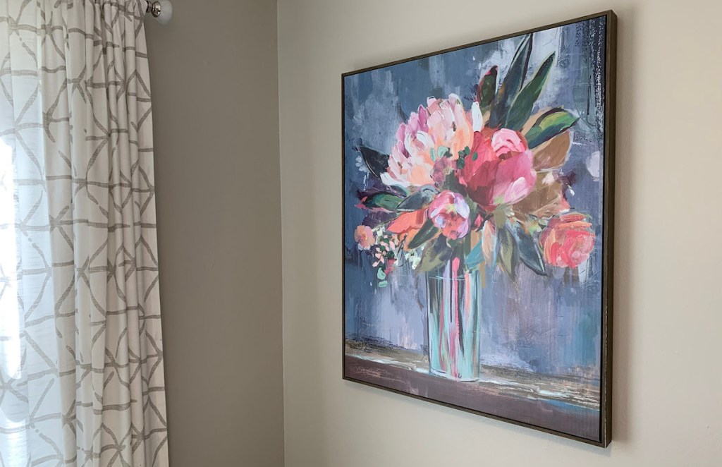 large floral artwork hanging on gray wall with curtains