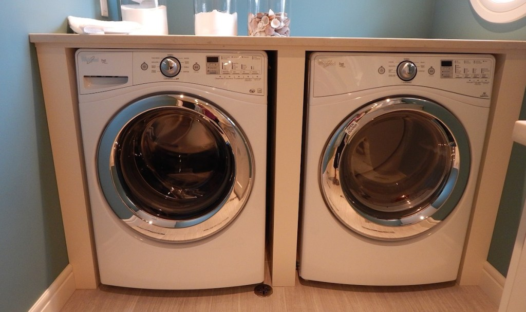 side by side front loading washer and dryer machines in laundry room