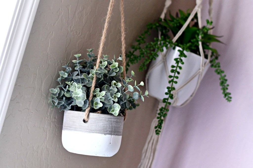 two hanging faux planters with green plants inside