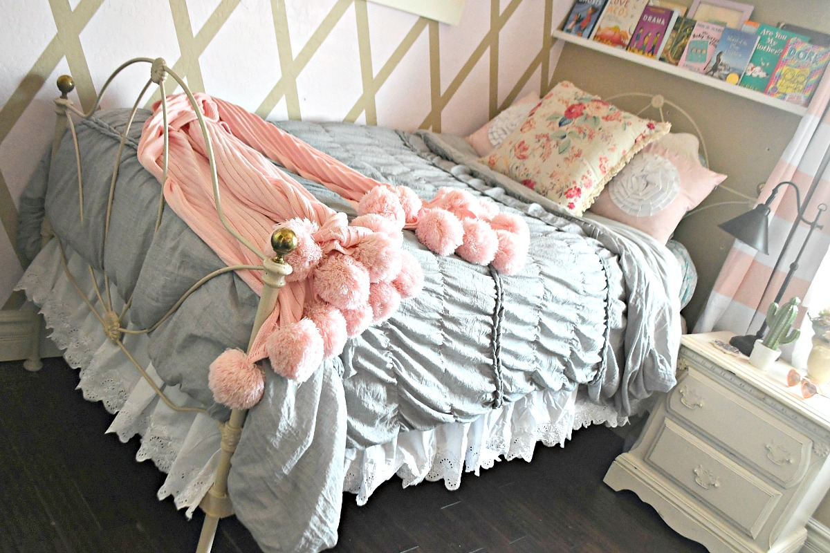 girls bed with gray comforter and pink pom pom blanket