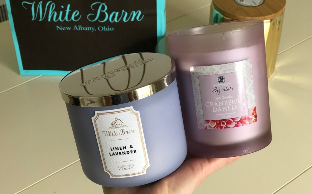 hand holding two purple floral scented candles with white barn bag in background