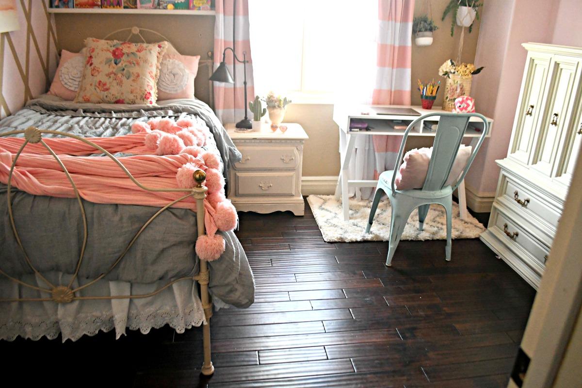 feminine bedroom with bed pink blanket and homework desk