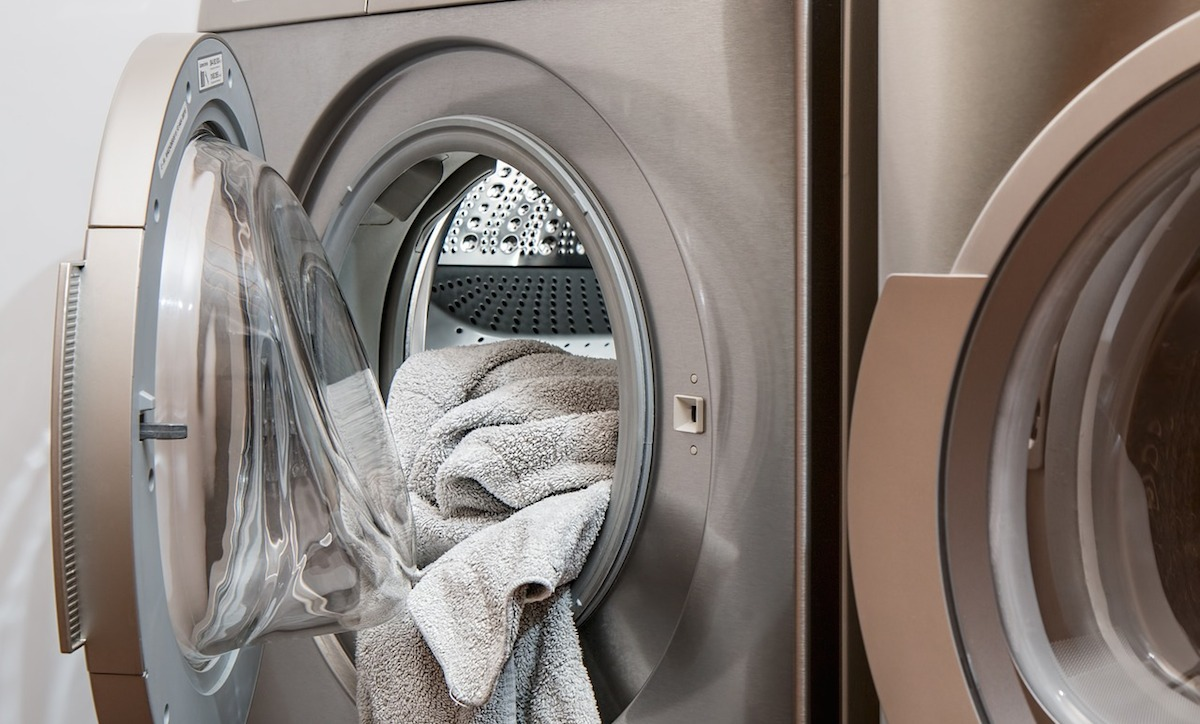 open front load washing machine with towel hanging out of door