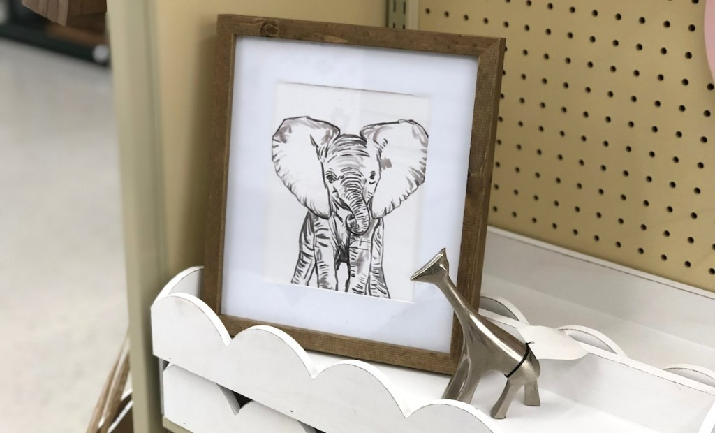 elephant framed print on white scallop shelf with metal silver giraffe statue