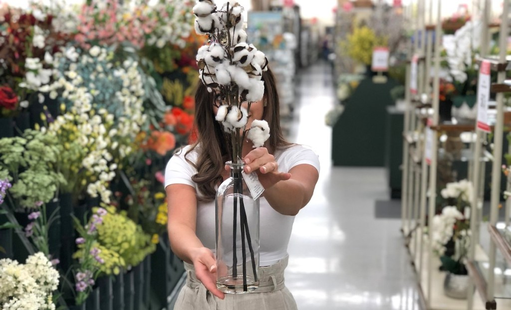 sara holding cotton stems in glass vase in floral aisle at store