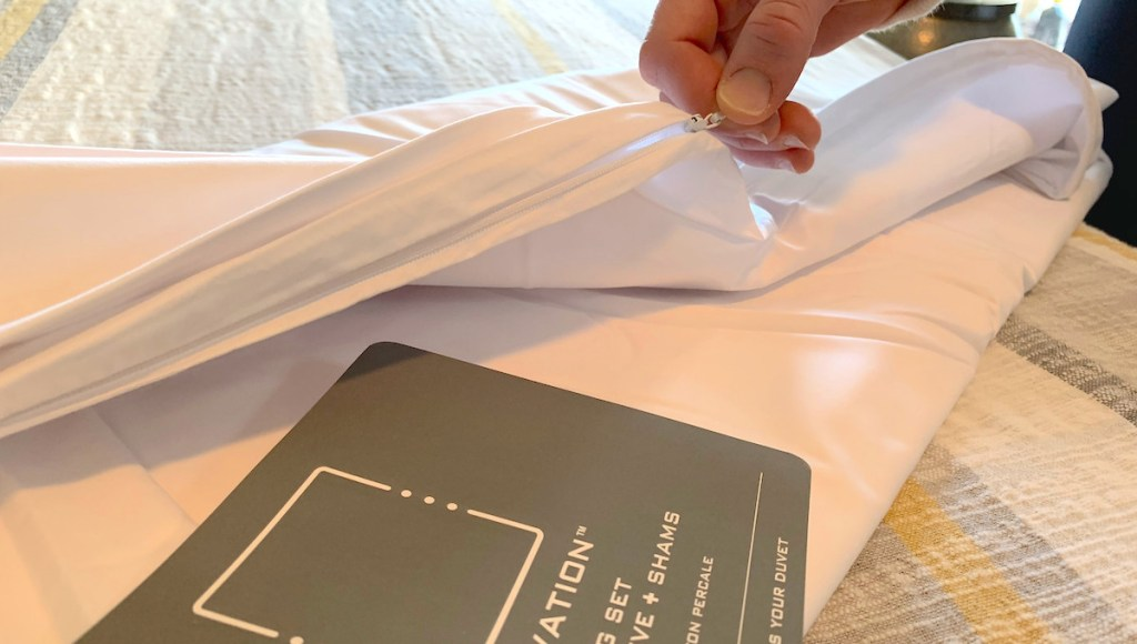 hand pulling on white zipper on blanket and gray paper with white writing