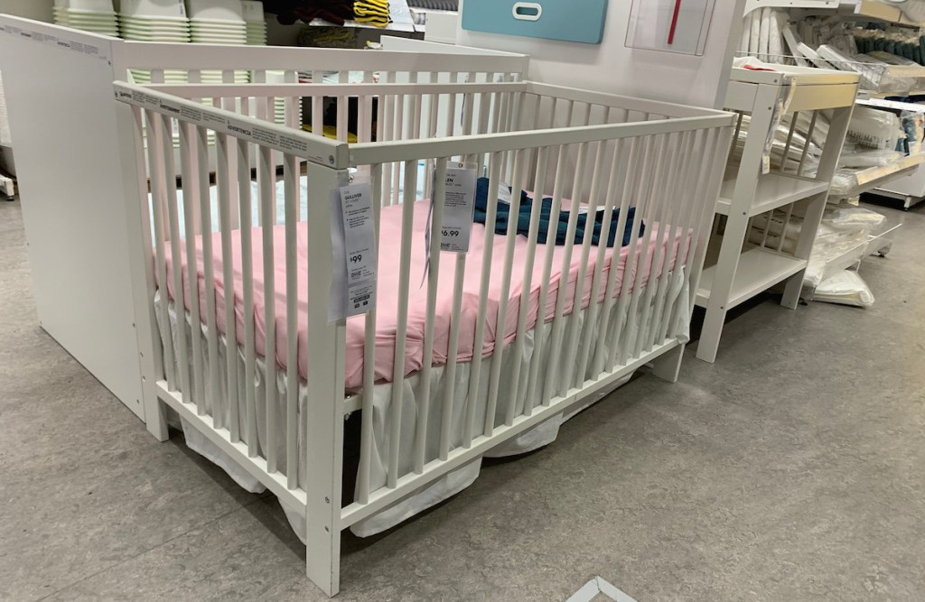 white crib with pink fitting sheet with price tags on front