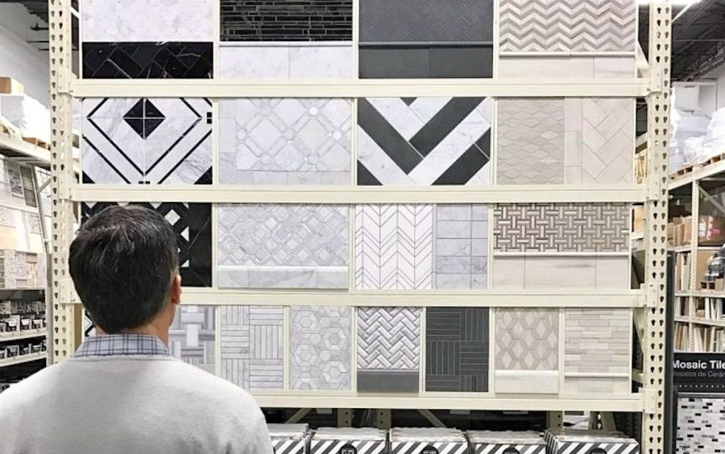 man standing in front of tile wall with different varieties of mosaic tile samples