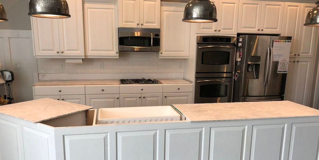 white kitchen cabinets with temporary plywood countertops and stainless steel appliances