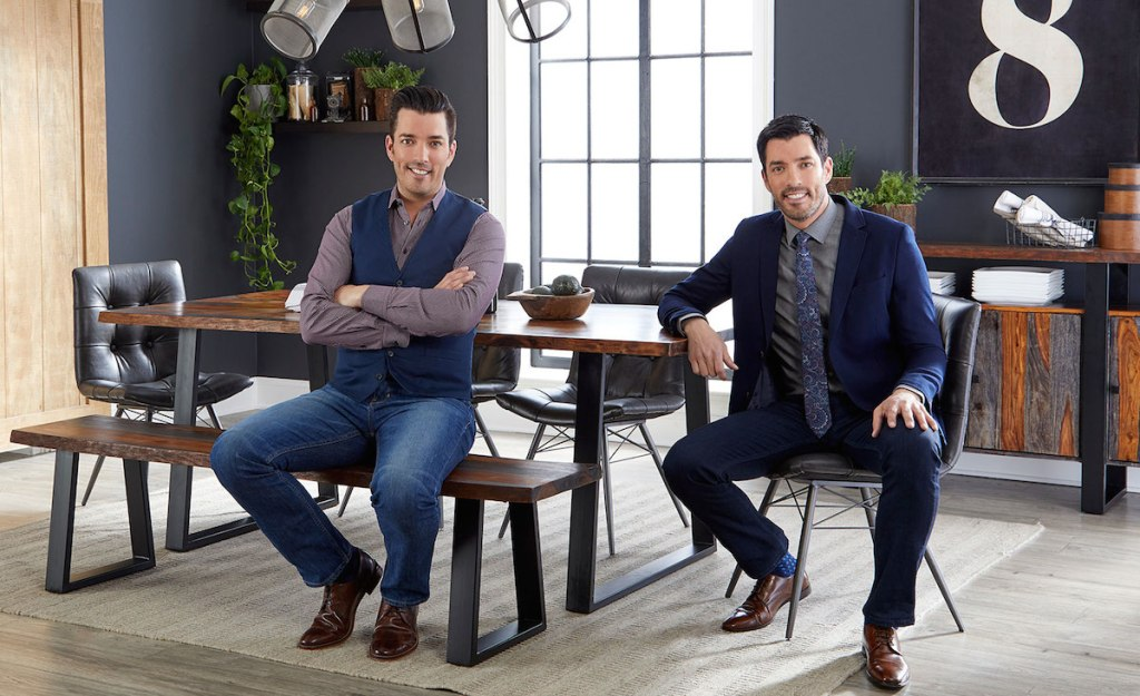drew and johnathan scott dressed in suits sitting at wood dining table set