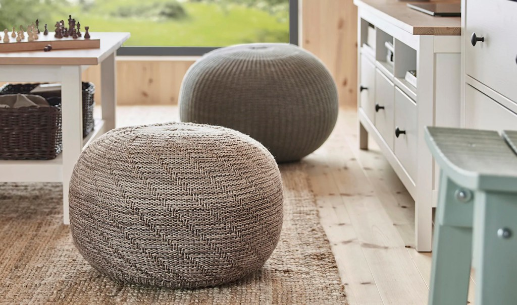 two round pouf ottomans sitting on jute rug with white cabinets to the right