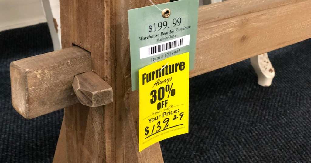 close up photo of wood with yellow furniture sale sign