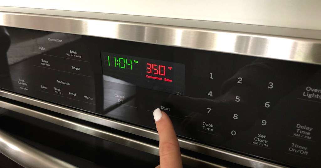 finger pointing at red 350 degrees convection bake button on wall oven