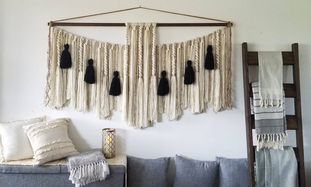 black and cream wall hanging on white wall gray couch with pillows and ladder on wall