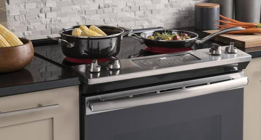 electric stainless steel and black range with pot and pan cooking corn on the cob