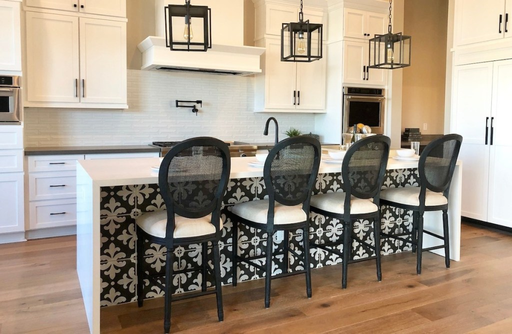 white kitchen cabinets with bold black round rattan barstools