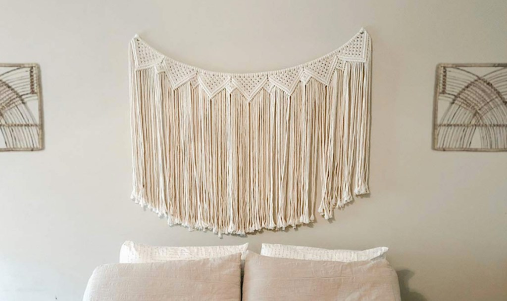 cream colored macrame wall hanging banner on gray wall with bed and pillows below