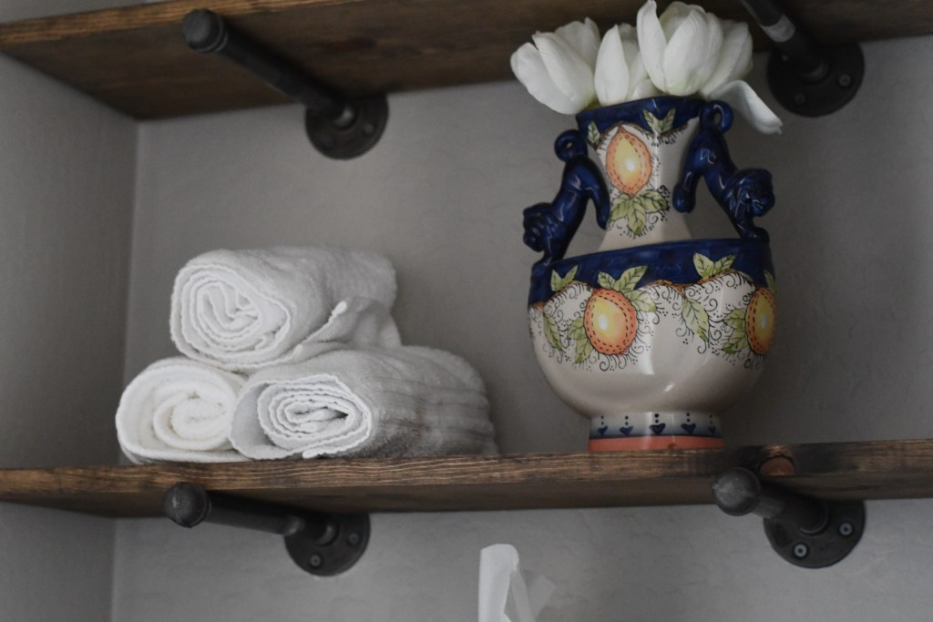 rustic open shelves with vase and towels