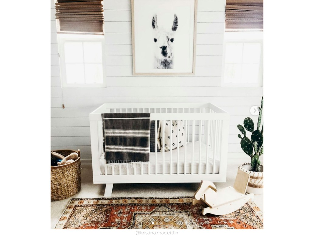 shiplap wall in nursery with huge llama artwork two windows a white crib and vintage style rug