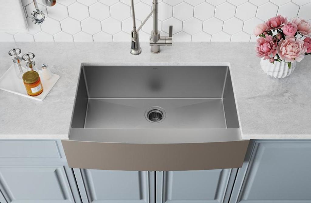 stainless steel sink with white countertops blue cabinets and white backsplash