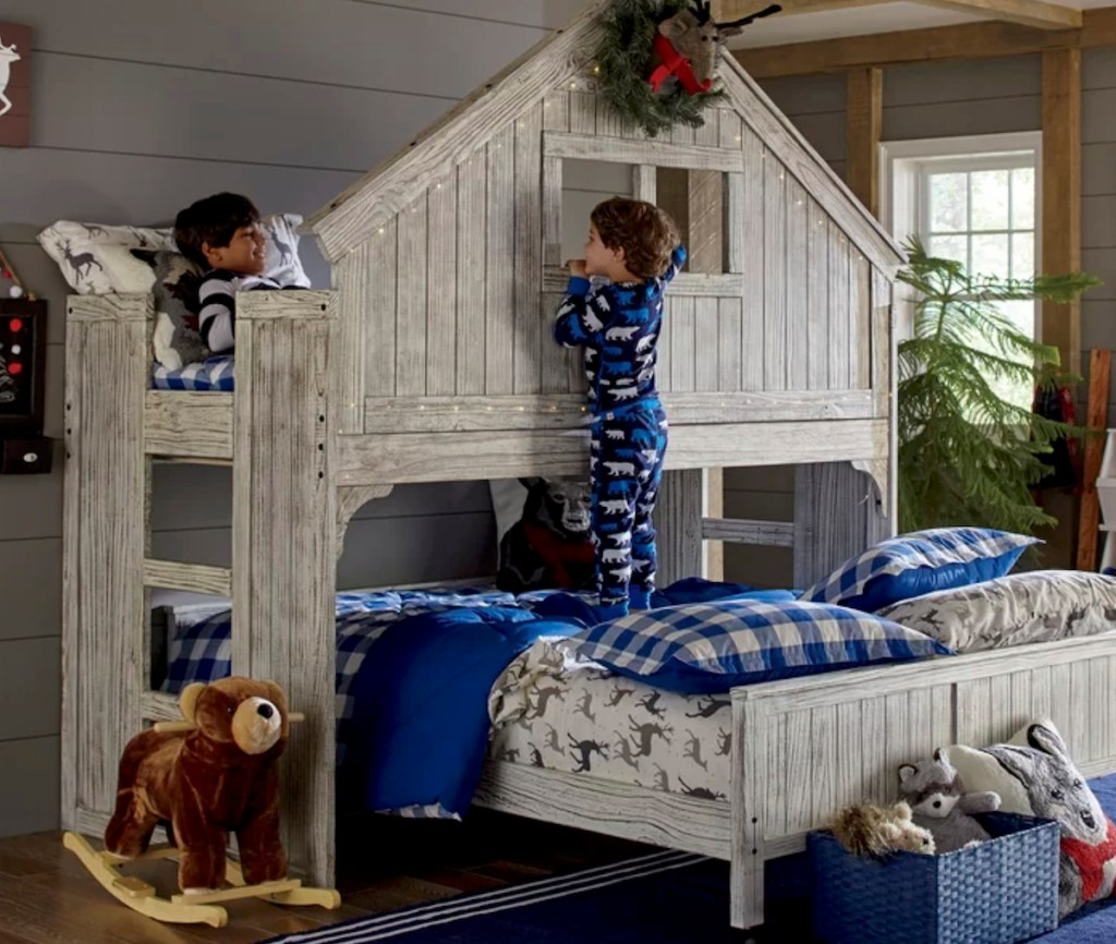 two boys playing on a twin over full wooden bunk bed