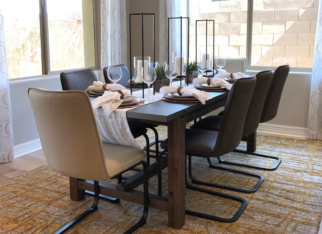dining room with table and chairs with dishes tall candles