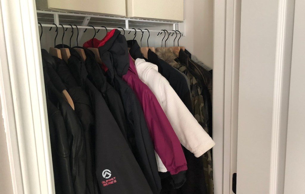 small coat closet with jackets hanging inside