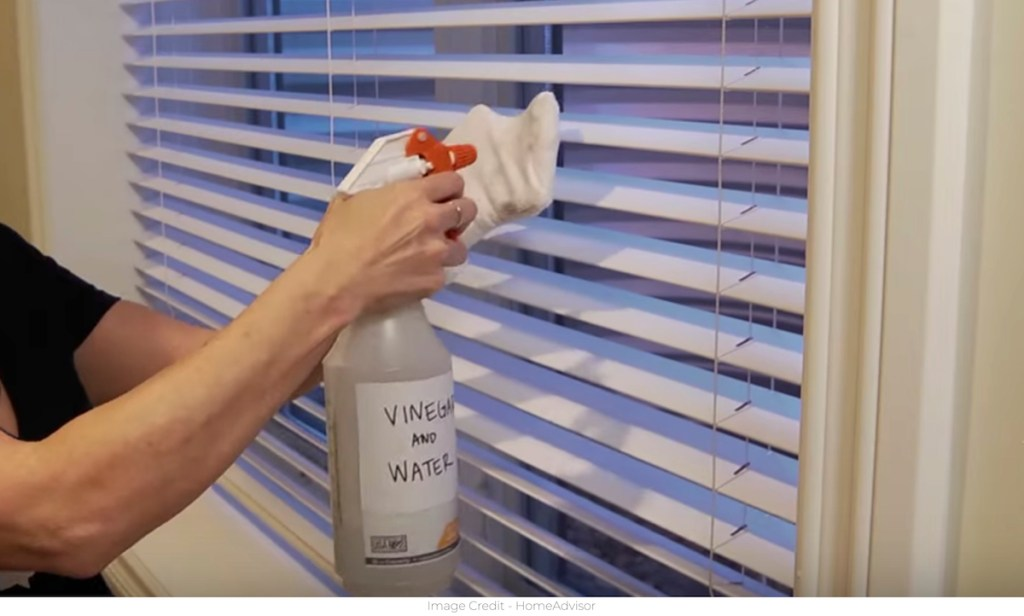 hand with white sock and spray bottle cleaning blinds