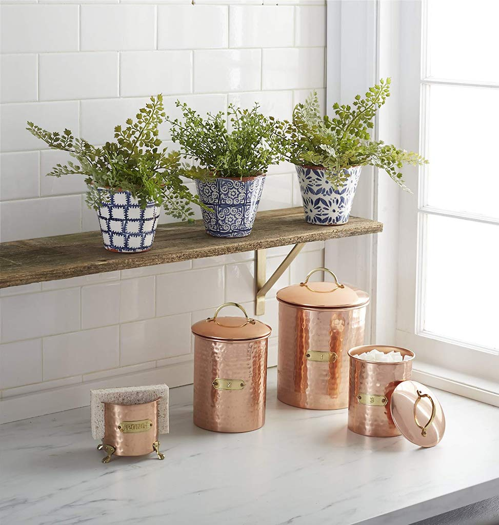 plants on shelf with copper containers and sponge holder