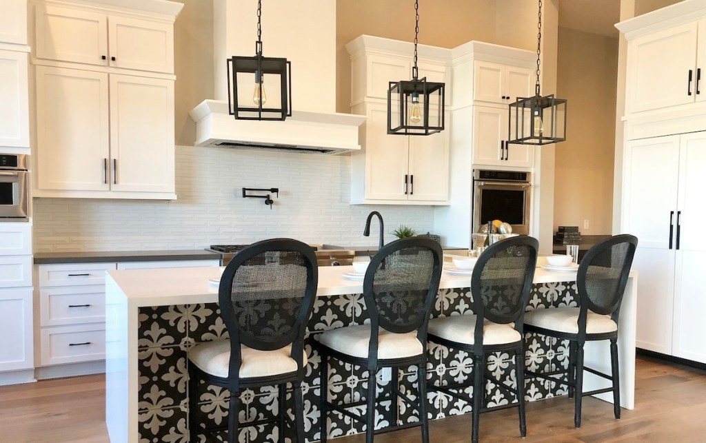 tall white kitchen cabinets with large island and stools