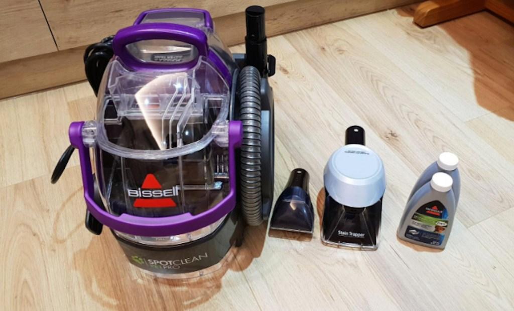 purple bissell spot clean vacuum sitting on wood floor