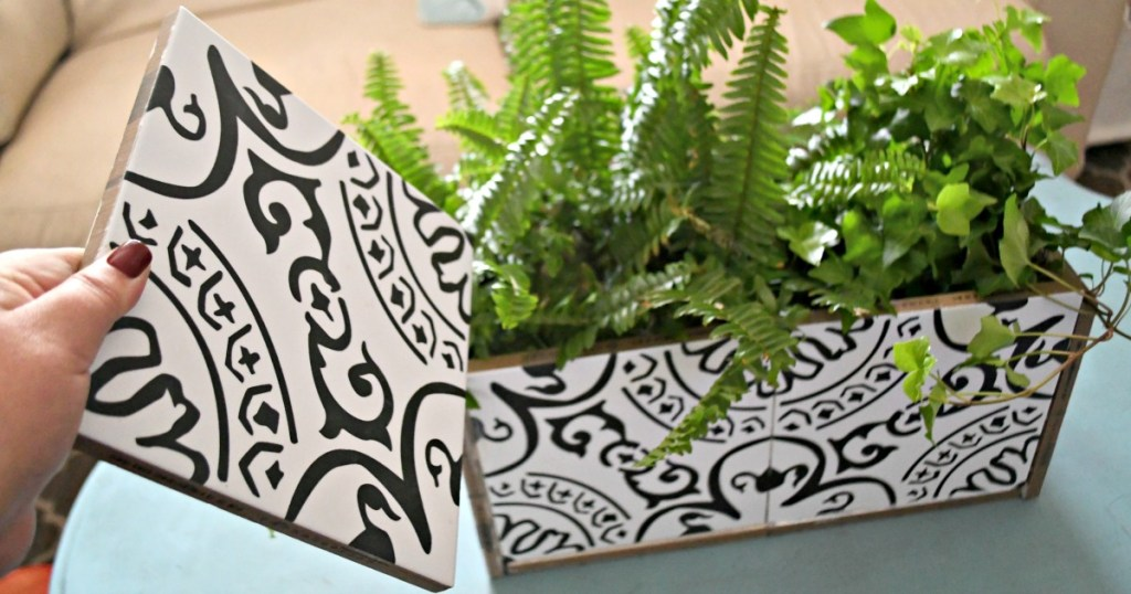 holding a tile to make a diy planter