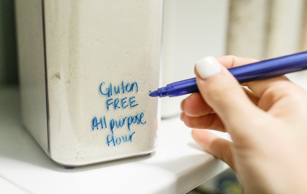 hand using blue marker on plastic container