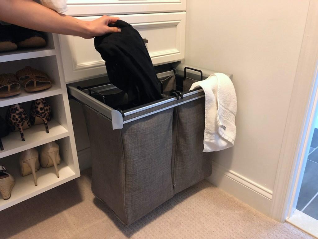 hand holding black clothing over laundry sorter